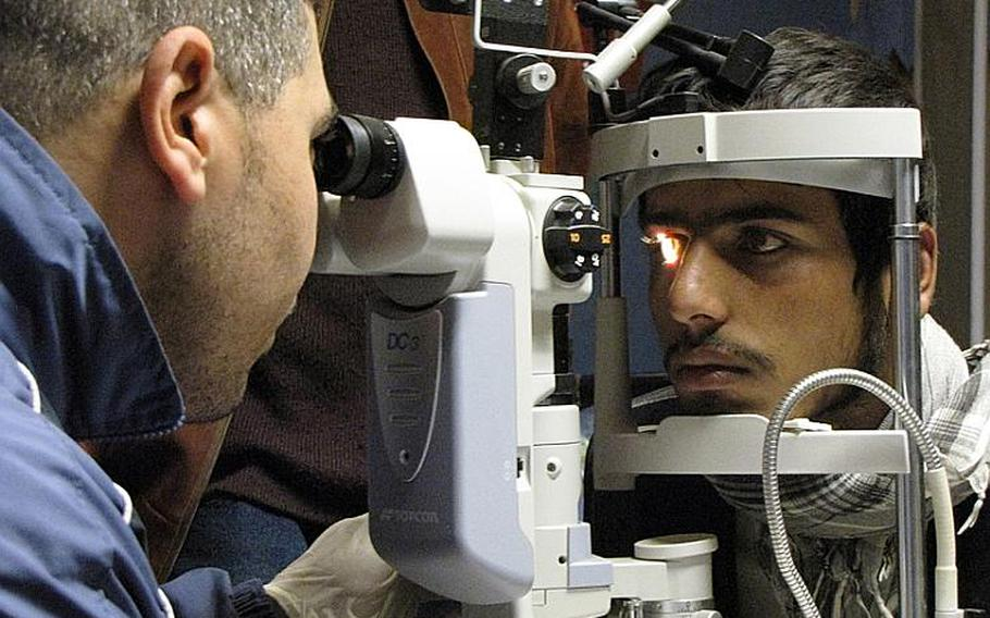 Dr. (Maj.) Hassam Mohamed of the Egyptian army, examines the eyes of Kamal, a 16-year-old local Afghan at the Egyptian Field Hospital at Bagram Air Field in Parwan province, north of Kabul.  Kamal suffered eye trauma in a motorcycle accident four years ago.