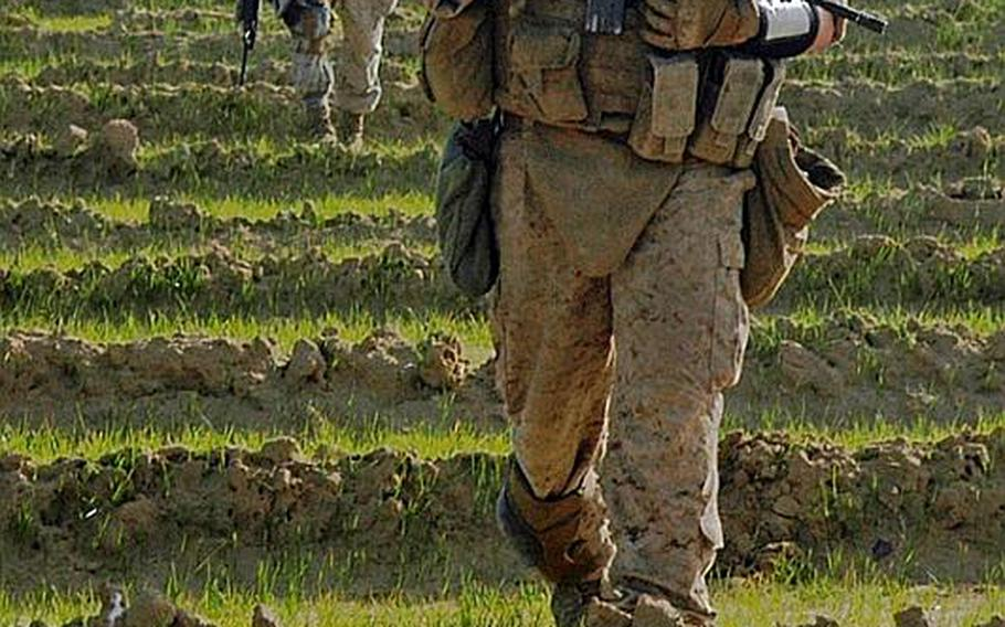 Marines walk in a line to avoid stepping on mines. Pressure-plate bombs is the biggest threat for the artillery Marines working like infantrymen out of Fiddler's Green, an outpost in central Helmand province.