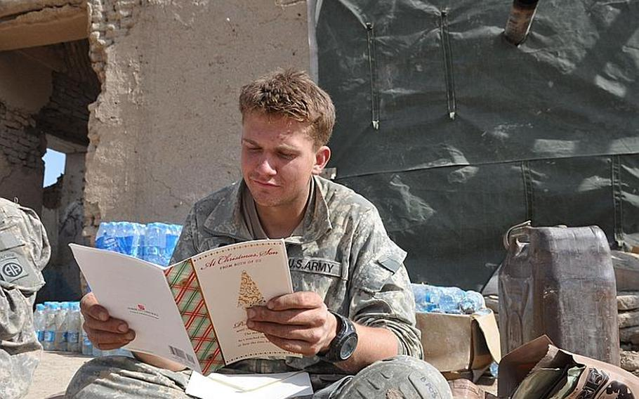 Spc. Nic Carey reads a Christmas card he received on Feb. 18 at Objective Prius, where U.S. and Italian soldiers live in the bombed-out compound with Afghan security forces. The coalition and government forces captured Prius during a major operation in late December.
