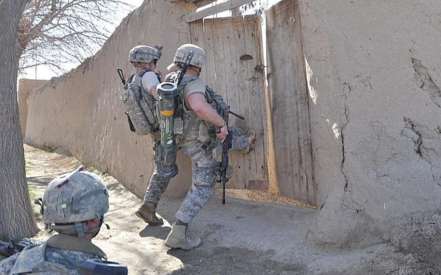 U.S. paratroops kick in the door of a compound near a field where they'd just taken insurgent fire during a patrol on Feb. 22 in Bala Murghab.  The soldiers have fought intense battles to win key terrain in this insurgent-controlled valley in Badghis province.