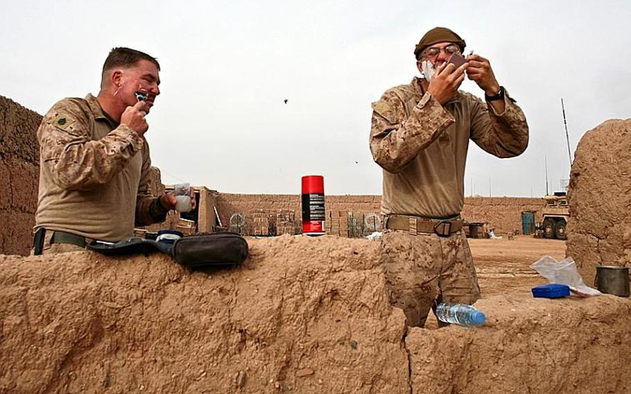There's no running water at Combat Outpost Coutu, so Staff Sgt. Kevin Barlow, 31, of Richmond, Va., and Lance Cpl. Christopher Bello, 23, of Jacksonville, N.C., shave with just ounces of water each in a plastic water bottle and metal canteen cup.