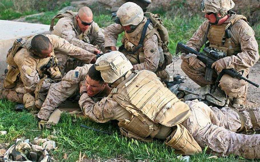 Lance Cpl. Matthew W. McElhinney is hit just above the right buttock and below his bulletproof vest. There is no exit wound, and the extent of his injury is unknown. But he is bleeding profusely and in a lot of pain as his comrades work to stop the loss of blood and comfort him at the same time.