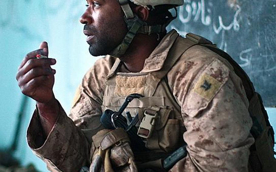 With his patient taken away, Navy Corpsman Jonathan Duhart takes a smoke break as he and his Marines try to dissect how the attack happened and how their fellow Marine was hit.
