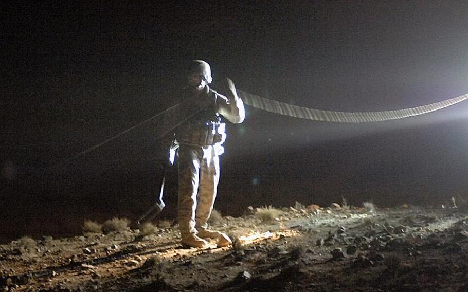 Air Force Tech. Sgt. Jacob Monelo, 35, of Sacramento, Calif. traces the command wire of a bomb discovered in Kandahar province on Aug. 26.
