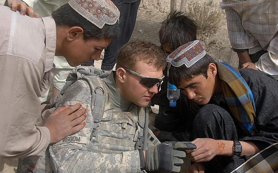 Pfc. Nicholas Wisdom of the 2nd Stryker Cavalry Regiment shows teenagers in Latek village his U.S. Army ID card during a patrol on Sept. 13.