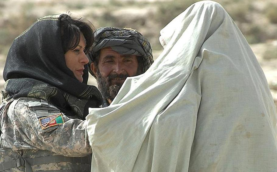 Female Engagement Team Laila Khoshnaw searches a woman being taken to a medical clinic on a donkey by her husband in Zabul province.