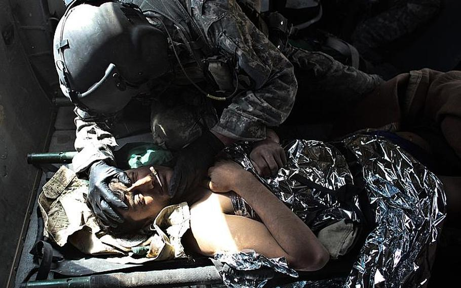 Sgt. Patrick Schultz, 31, a flight medic with the 101st Combat Aviation Brigade's Task Force Shadow, treats an Afghan soldier who was wounded in a Taliban attack south of Kandahar, Afghanistan, on Sept. 21, 2010.