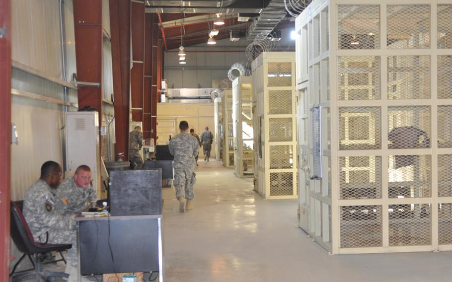 U.S. soldiers serving as prison wardens sit outside the caged cells where Afghan detainees are held at the U.S. Detention Center in Parwan on Nov. 24, 2010.