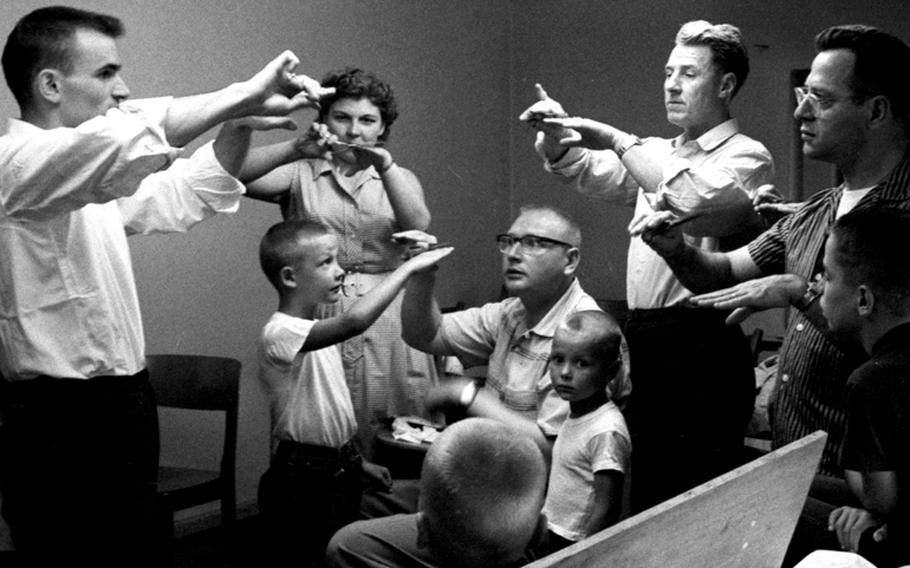 Participants in a barber course at Wiesbaden, Germany, in 1959 go through the basics of trimming technique.