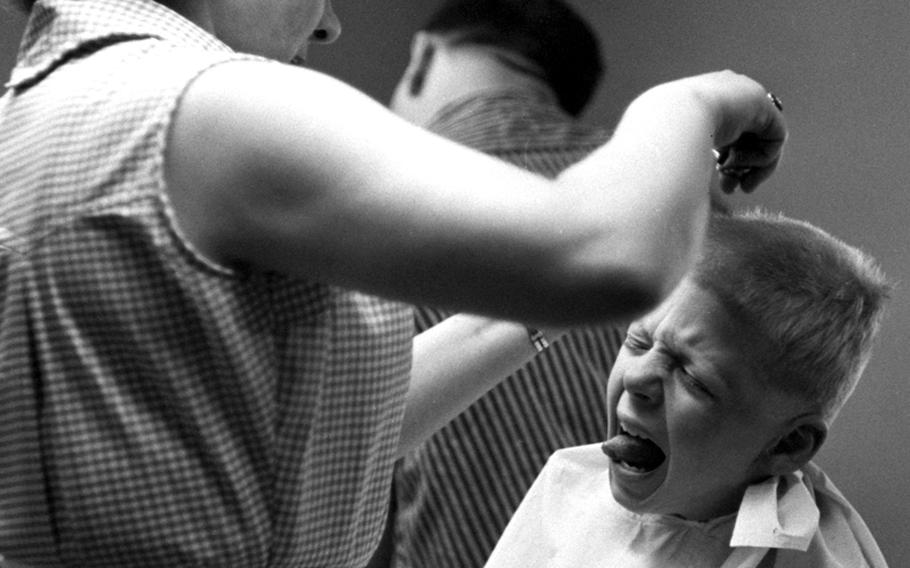 A test subject in a hair-cutting class at Wiesbaden, Germany, in 1959 finds that there's a learning curve for parents taking the course.