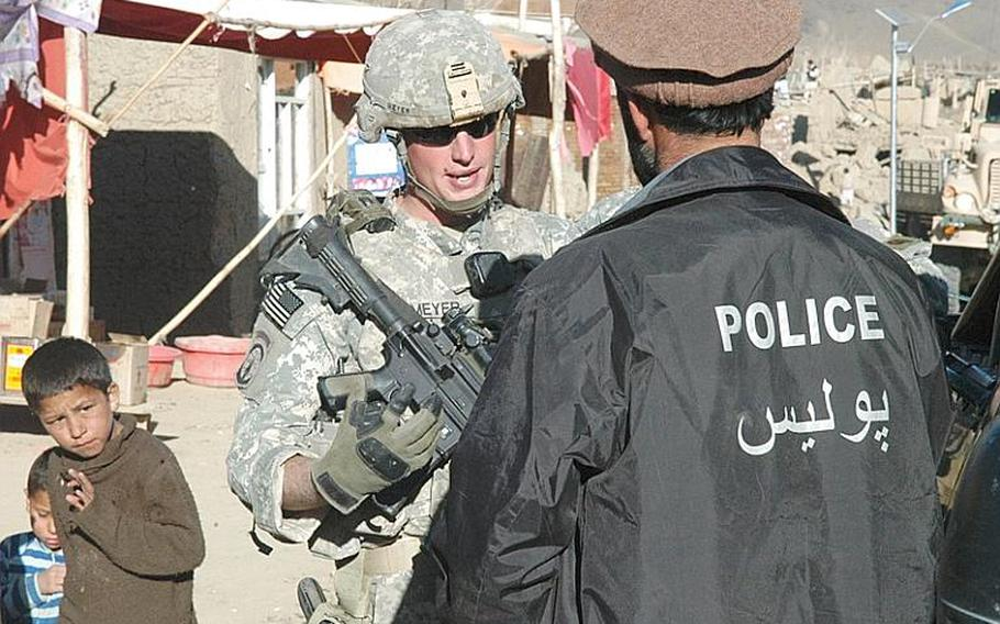 Cpl. Eric Meyer of the 118th Military Police Company talks in late 2009 with an Afghan policeman in Jalrez valley in eastern Afghanistan's Wardak province.