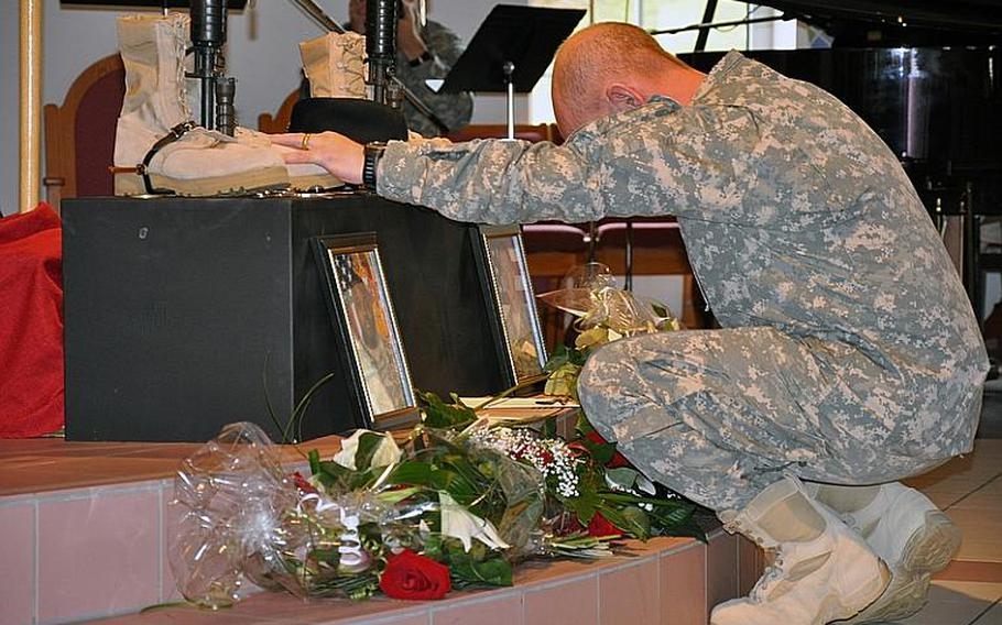 A soldier pays his respects to Cpl. Donald R. Mickler Jr.and Pfc. Rudy A. Acosta after a memorial service Thursday at the Cavalry Chapel on Rose Barracks in Vilseck, Germany. Both soldiers were killed March 19 in Afghanistan. They were posthumously promoted.