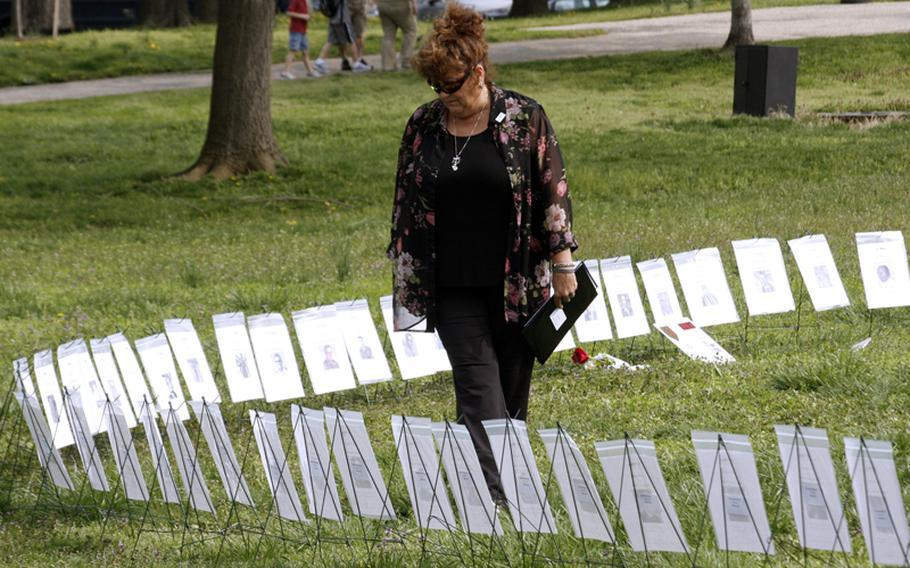 Suzanne Blohm-Weber walks along a row of tributes to Vietnam veterans before Monday's In Memory Day observance on the National Mall in Washington, D.C. Her husband, Michael Anthony Weber, is one of 93 veterans whose names were added to the In Memory Honor Roll.