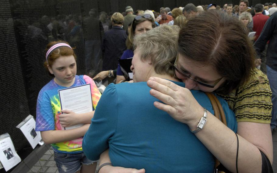 Relatives of Vietnam veteran Don LaVerne Crum embrace as they remember him at the Vietnam Wall. Crum, who died in 2008, is one of 93 veterans whose names were added to the In Memory Honor Roll.