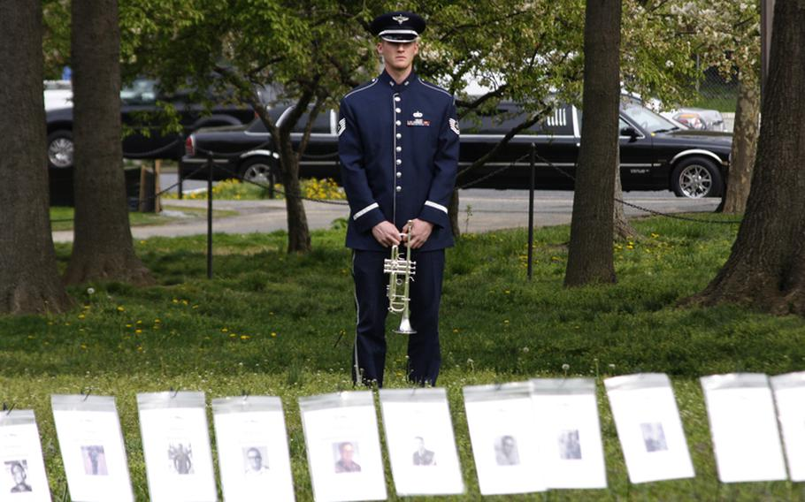 Air Force Tech. Sgt. Nathan Clark stands behind a row of tributes to Vietnam veterans as he waits to play Taps at Monday's In Memory Day observance.