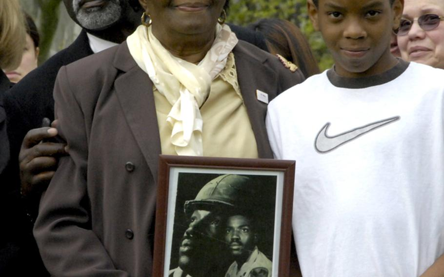 Vietnam veteran Gregory Franklin Brown is honored by his widow Lavonia, brother Michael, and son Antoine during Monday's In Memory Day observance. Brown, who died in 2009, is one of 93 veterans whose names were added to the In Memory Honor Roll.