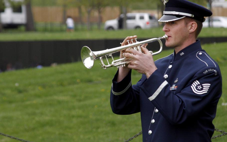 With the Vietnam Wall in the background, Air Force Tech Sgt. Nathan Clark plays Taps.