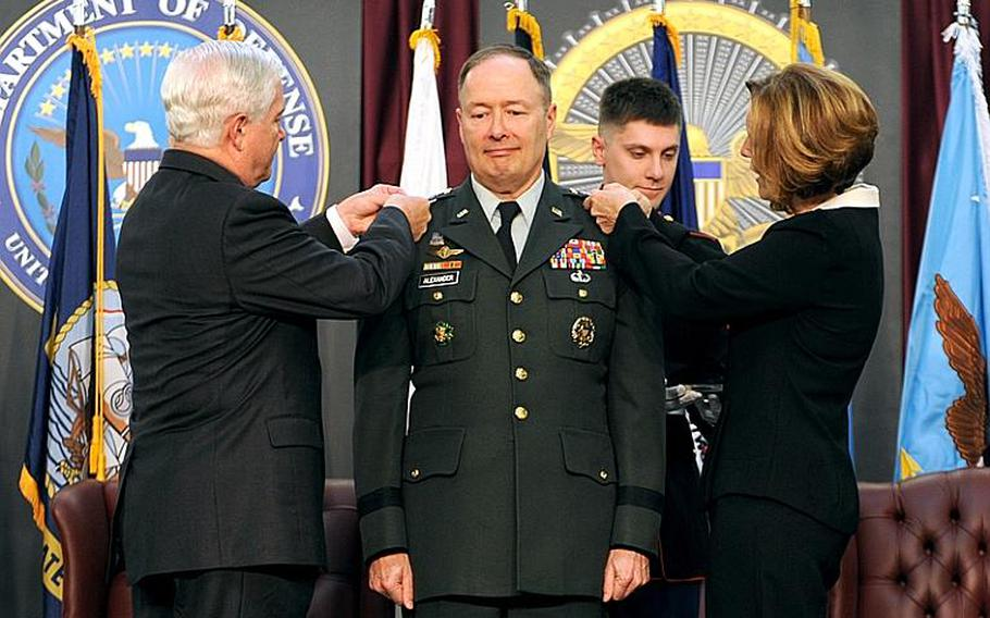 Secretary of Defense Robert M. Gates and Deborah Alexander pin on the new four star rank pins of U.S. Army Gen. Keith Alexander during his promotion and activation ceremony of U.S. Cyber Command, which Alexander will command, at Fort Meade, Md., May 21, 2010.