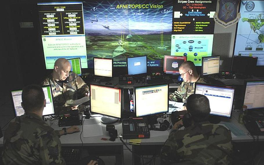 Capt. Jason Simmons and Staff Sgt. Clinton Tips update anti-virus software for Air Force units to assist in the prevention of cyberspace hackers in this 2007 photo at Barksdale Air Force Base, La.