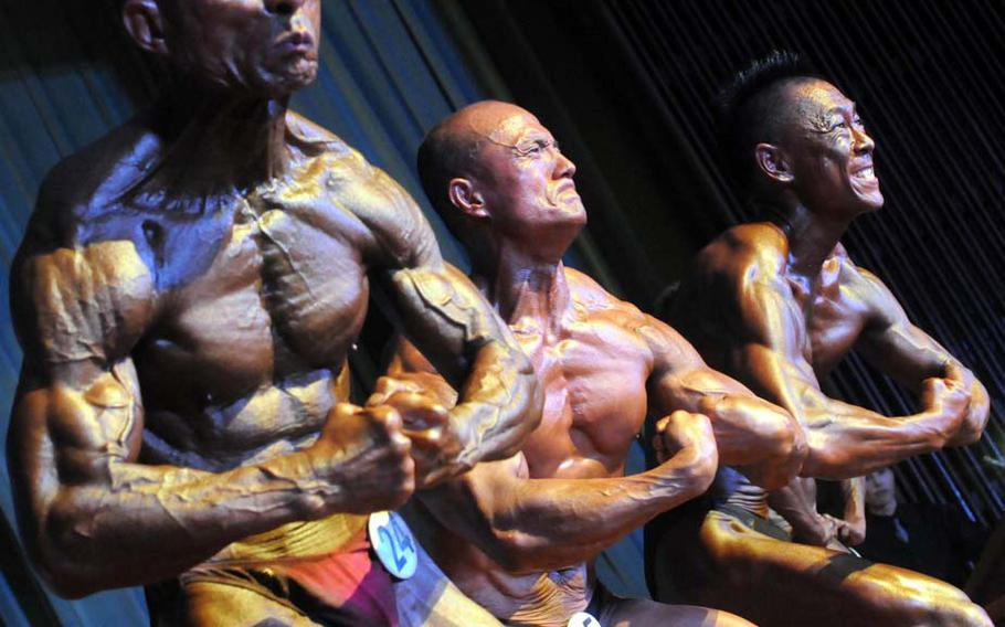 Men's masters competitors Hidekazu Taba, Mitsuhiro Gima and Takashi Omine pose down during Sunday's 5th Pacific Muscle Classic bodybuilding, fitness and figure competition at Keystone Theater, Kadena Air Base, Okinawa. Taba won the men's masters title.