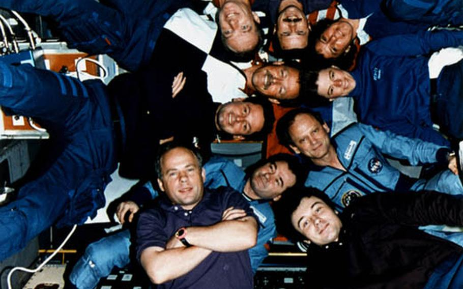 Inside the Spacelab Science Module, the crews of STS-71, Mir-18 and Mir-19 pose for the traditional inflight picture.