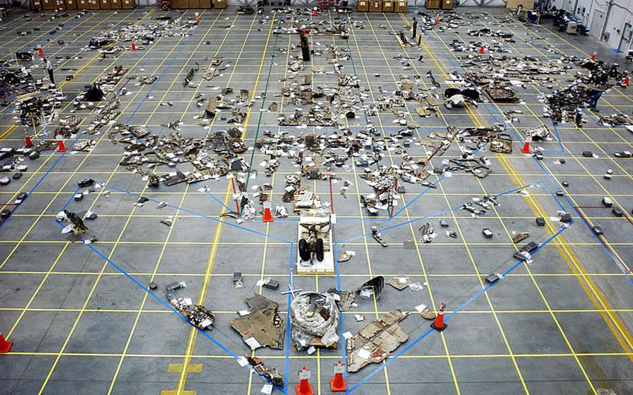 Columbia shuttle debris forms the rough shape of the orbiter in a hangar at Barksdale AFB in 2003.