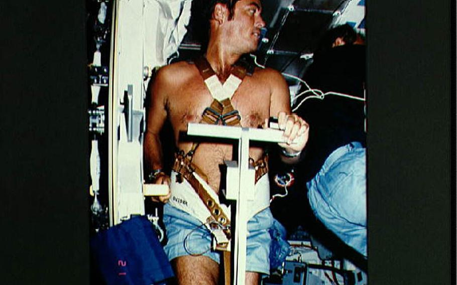 On middeck in front of open airlock hatch in 1983, commander Robert Crippen, restrained by harness, exercises on treadmill as fellow crew members conduct other activities around him.