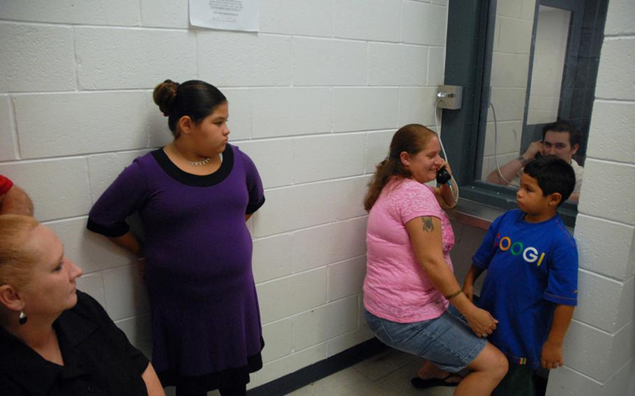 Former Army Sgt. Robert Quinones talks to his sister during family visiting hours in July at the Bulloch County Jail in Statesboro, Ga., where he is being held as a federal prisoner for a hostage incident at the hospital on nearby Fort Stewart. His family, including his sister's two children and his parents, visit him often.