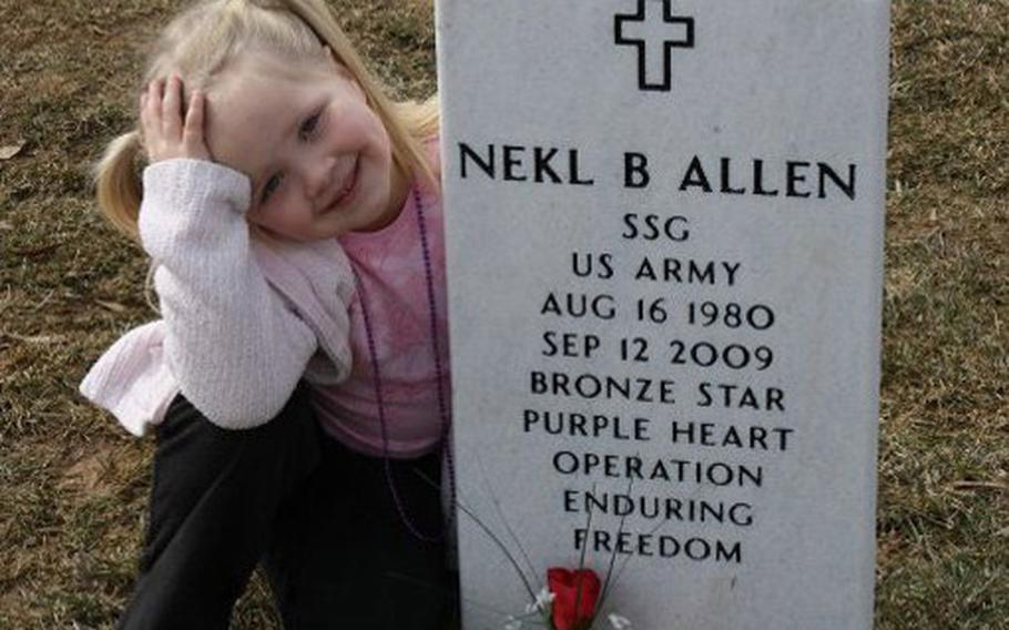 Staff Sgt. Nekl Allen's daughter, Grace, poses with his headstone at Arlington National Cemetery in February 2010. Allen was killed on Sept. 12, 2009, when a bomb exploded beneath his MRAP in Afghanistan.