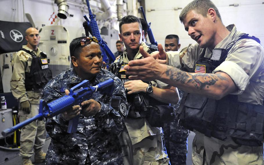 Petty Officer 2nd Class Nicholas Omeara teaches room entry techniques to members of the Philippine Coast Guard on board the Arleigh-Burke class guided missile destroyer USS Chung-Hoon during a Maritime Interdiction Operation training.