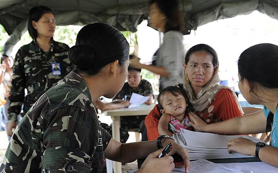 Armed Forces of the Philippines (AFP) nurses help with patient inprocessing of children waiting for cleft lip and cleft palate surgery at Camp Siongco Station in Maguindanao. The AFP's 6th Infantry Division in Maguindanao partnered with Joint Special Operations Task Force-Philippines (JSOTF-P), Knightsbridge International, Autonomous Region of Muslim Mindanao (ARMM) Department of Health, ARMM Department of Social Welfare and Development and local volunteer nurses to bring the non-governmental organization Operation Smile into the ARMM for the first time, and conduct close to 100 surgeries in four days.