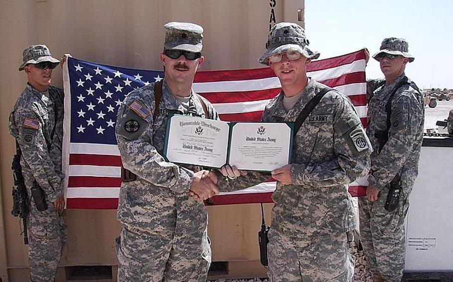 Then-Spc. James Coleman, right, re-enlists in Iraq during his third deployment in 2007.