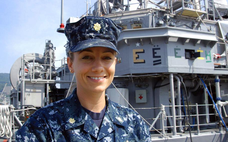 Despite enormous strides made by women in the Navy in the past 20 years, crewing a mine countermeasures ship remains one of the last positions to be integrated. Lt. Cmdr. Suzanne Schang of the USS Patriot is one of the first women to rise to command a forward deployed mine ship. Here she poses in front of the golden E for five consecutive years of excellence.
