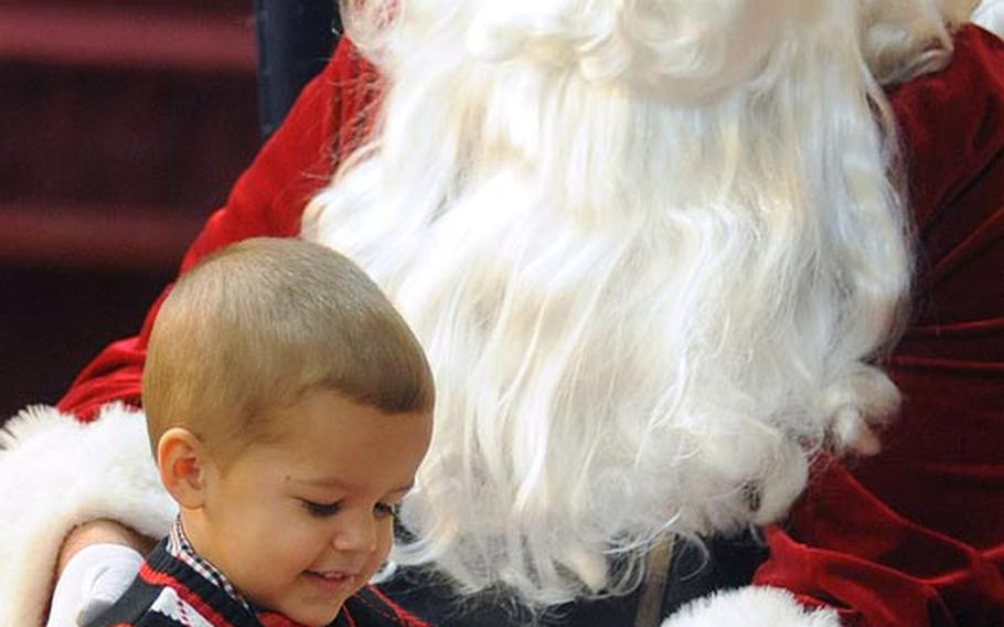 Romeo Hernandez, 2½, gives Santa five after getting his photo taken with the jolly one at the Baumholder tree-lighting ceremony Thursday night. Romeo was there with his mother Kimberly. His father, Spc. Rafael Hernandez Jr., is deployed to Afghanistan with Company C, 4th Battalion, 70th Armor Regiment.