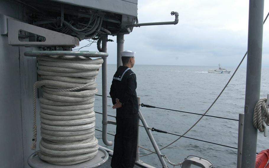 New cook Seaman Kevin Fan mans the rails on board the Avenger-class mine countermeasure ship USS Patriot en route to annual exercises with the Japanese in late October. Fan, a newly minted sailor and American citizen, joined the Navy after moving to the U.S. from China in 2004 and working in Calif. as a cook at a barbeque joint. He prefers to let his cooking do the talking for him.