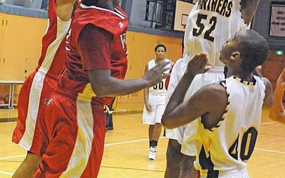Kadena Panthers forward Savon Woodie (52) puts up a shot over Nile C. Kinnick Red Devils defenders Cory Smoak and David Sledge (42) during Friday's pool-play game in the American School In Japan Holiday Basketball Classic in Tokyo. Kinnick beat Kadena 51-47.