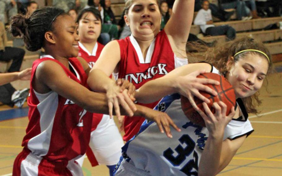 Yokota's Sydney Glover, right, battles Nile C. Kinnick's Ericka Carter, left, and Emily Stith for the ball during Tuesday's pool-play game in the Yokota High School Christmas Classic girls basketball tournament in Japan. Yokota won 48-41.