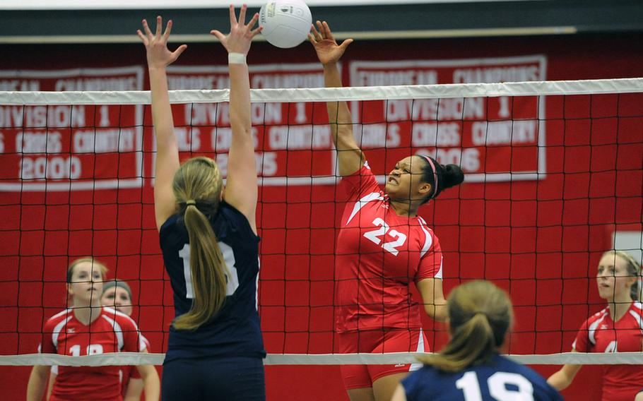 Kaiserslautern's Kalynn Richardson slams the ball over the net against the defense of Lakenheath's Eliza Evans in a Division I match at the DODDS-Europe volleyball championships. Kaiserslautern won the match 25-22, 20, 25, 25-19.