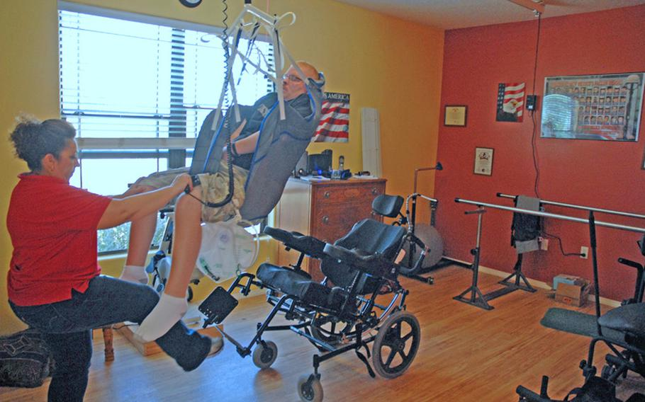 Erik's occupational therapist uses a track system in the ceiling to move him from the therapy table to his wheelchair.
