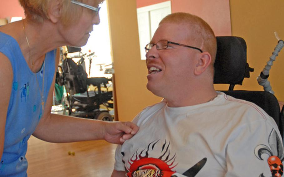 Christine Schei encourages her son during his therapy session in June 2012. She is supposed to take a break from caregiving while he's in therapy, but she often comes into the room to help for a few minutes before the therapist shoos her away.