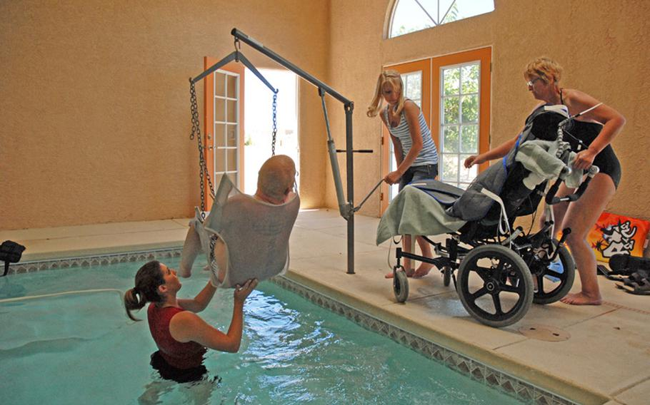 Getting Erik out of the pool after his water therapy is a group effort. His sister Anneka turns the crank to lift the sling from the water while his mom readies the wheelchair.