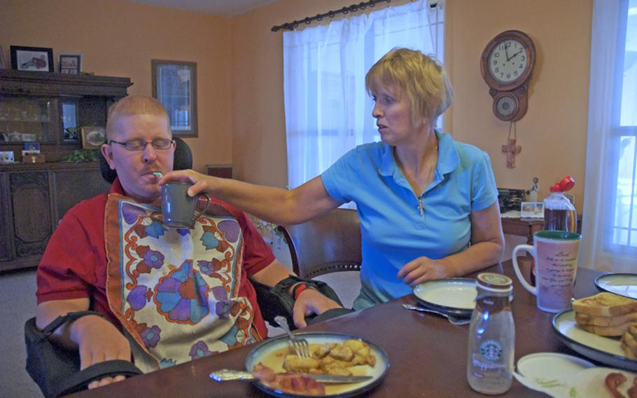 On a Saturday morning in June, Christine Schei's plate remains empty while she feeds her 28-year-old son, Erik, breakfast. Erik was shot in the head in Iraq in 2005 and has little use of his body.