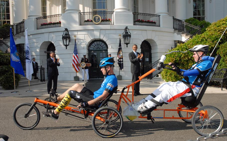 Erik Schei, far right, during the Soldier Ride at the White House in the spring. The medically retired Army sergeant, who was shot in the head in Iraq, is pulled by his brother, Spc. Deven Schei, on a specially made bicycle. Deven was wounded in Afghanistan.