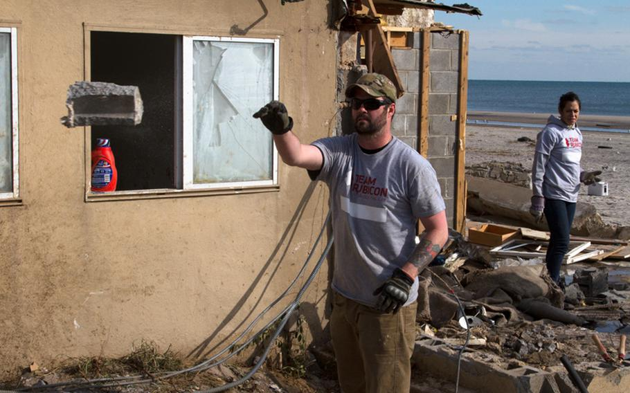 Veteran Dan Gorman with Team Rubicon tosses rubble from the shell of a ruined home near the New York shoreline on Nov. 5. Volunteers with the disaster relief group have been providing transportation, clean-up, and other support services to residents hit hard by last month's superstorm.