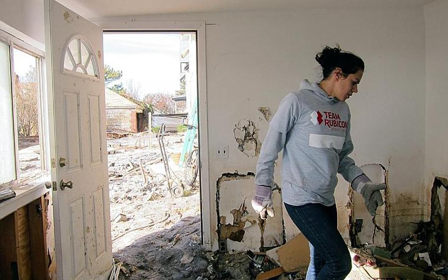 A veteran volunteer with Team Rubicon sorts through the rubble of a home in the Rockaways in New York that was destroyed by Superstorm Sandy last month. Officials with the disaster relief group said many homes remain inaccessible in the area, because of the extensive storm damage.