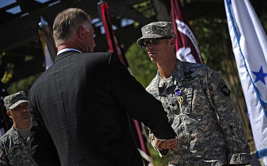 Deputy Secretary of Defense William J. Lynn III congratulates U.S. Army Spc. Deven Schei after presenting him the Purple Heart during a ceremony at the Warrior and Family Support Center at Brooke Army Medical Center in San Antonio, Texas, Sept. 28, 2011.