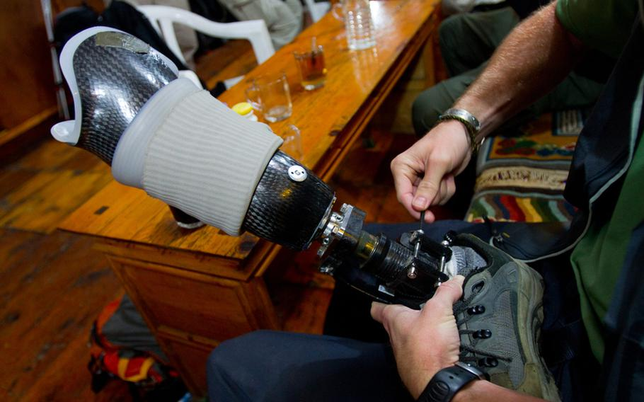 """Veteran Matt Nyman makes some adjustments to his prosthetic before heading out on the trail. Nyman was among a group of wounded veterans who took part in a Himalayan mountain climb, which is the subject of the new documentary film """"High Ground."""""""
