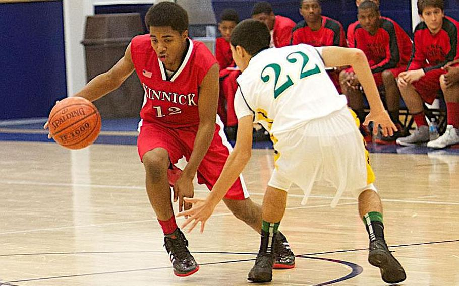 Casuan Caudle of Nile C. Kinnick looks to dribble past Ismail Leon of Robert D. Edgren during Friday's DODDS Japan season-opening high school basketball game at Misawa Air Base, Japan. Edgren edged Kinnick 57-53 in overtime.
