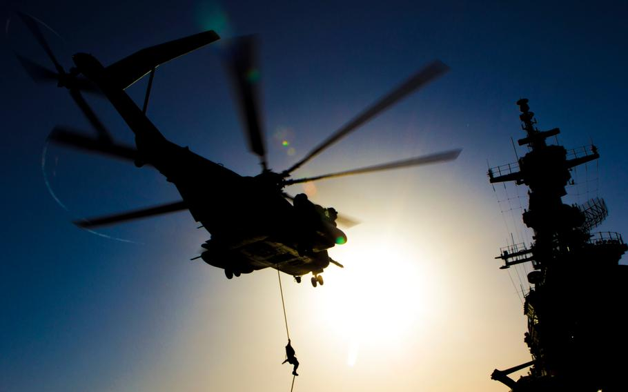 A U.S. Marine assigned to Battalion Landing Team 3/2, 26th Marine Expeditionary Unit, fast ropes from a CH-53 Super Stallion assigned to Marine Medium Tiltrotor Squadron 266, 26th MEU, during familiarization training on the flight deck of the USS Kearsarge, at sea, June 30, 2013.