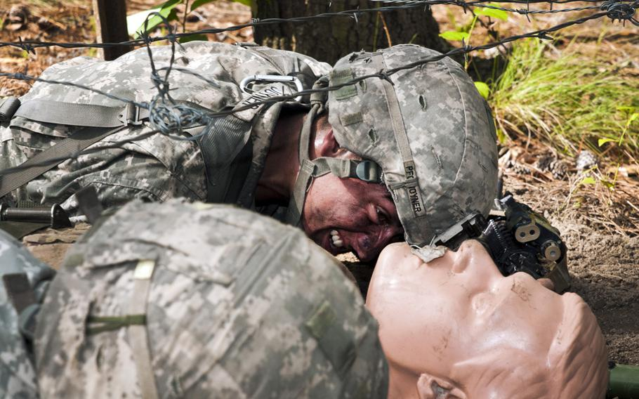Army Spc. Kyle Joyner, left, a line medic, maneuvers a simulated casualty underneath barbed wire during test for the Expert Field Medical Badge on Fort Bragg, N.C.